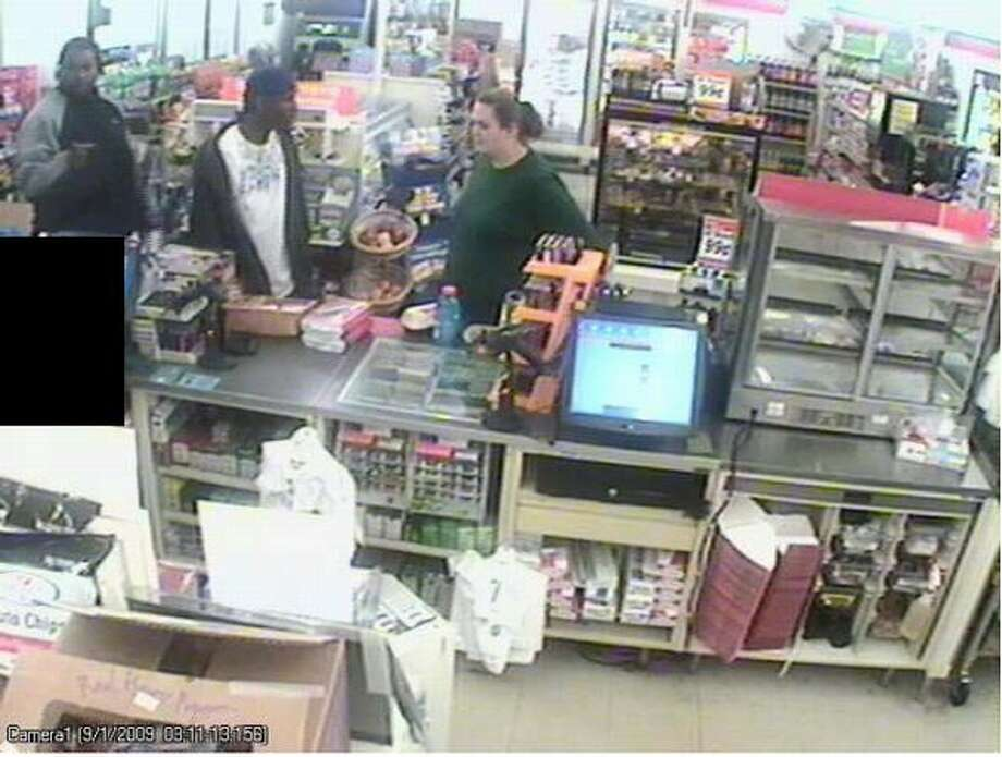 This Sept. 1 surveillance image shows two of the three men police suspect in a string of recent robberies. The woman accompanied the men at the convenience store, which police said was not robbed. A clerk is blacked out. (Seattle Police Department photo) Photo: /