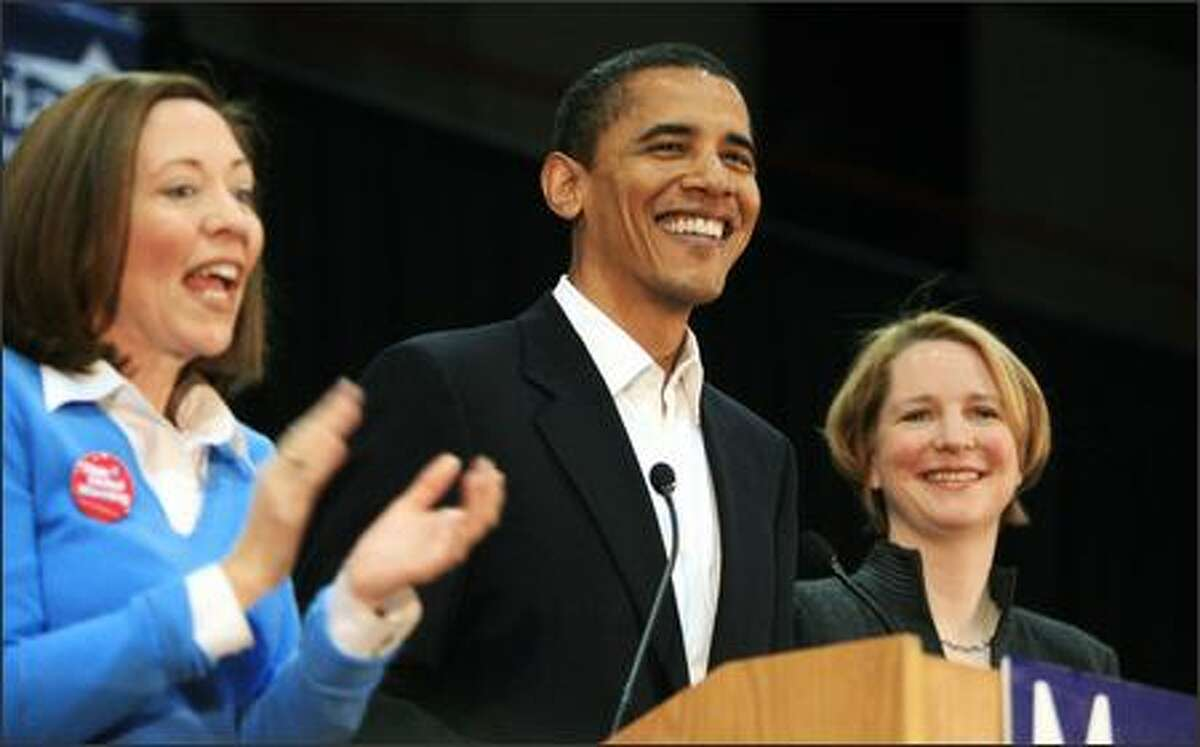 """Then-Sen. Barack Obama, D-Ill., is flanked by Sen. Maria Cantwell, D-Wash. (left) and U.S. House candidate Darcy Burner after he was introduced at Bellevue Community College on Oct. 26, 2006. The school has since dropped the word """"Community"""" from its name."""