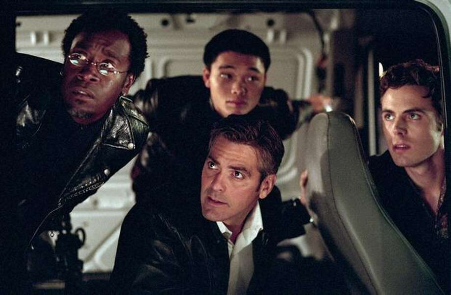 """From left, Don Cheadle, Shaobo Qin, George Clooney and Casey Affleck in a scene from the 2001 heist caper """"Ocean's Eleven."""" Photo: / Warner Brothers"""
