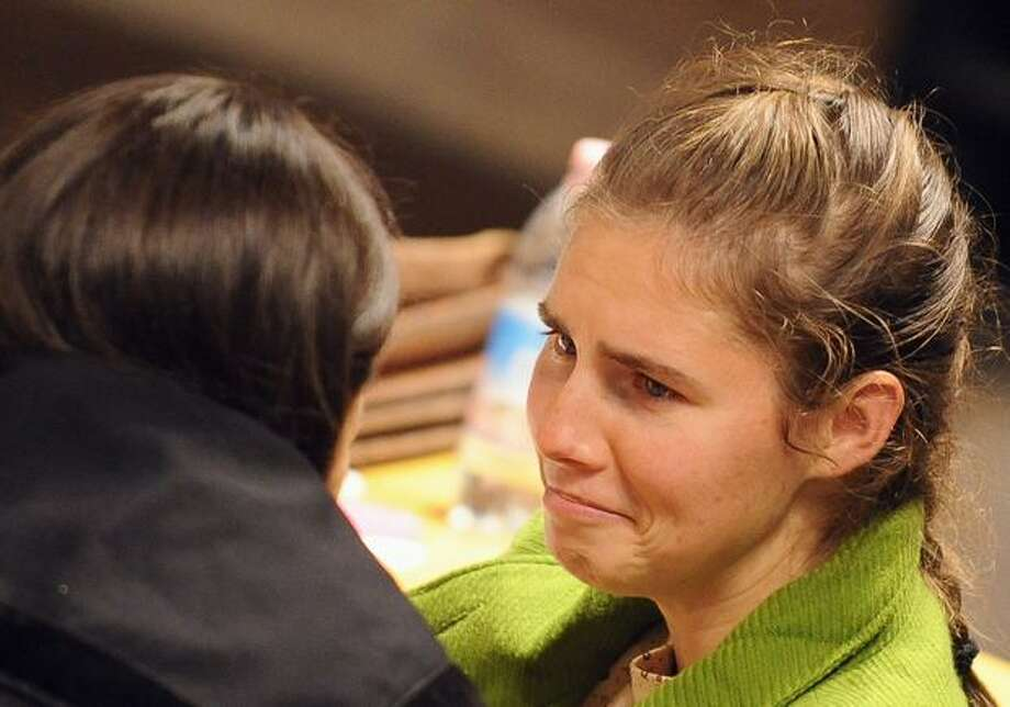 "Amanda Knox talks with one of her lawyers during the closing arguments of her trial for murdering her roommate, Meredith Kercher. Knox asked a jury not to put the ""mask of a murderer"" on her as she and her boyfriend made emotional final appeals denying the murder of British student Meredith Kercher. (Alberto Pizzoli/AFP/Getty Images) Photo: / Getty Images"