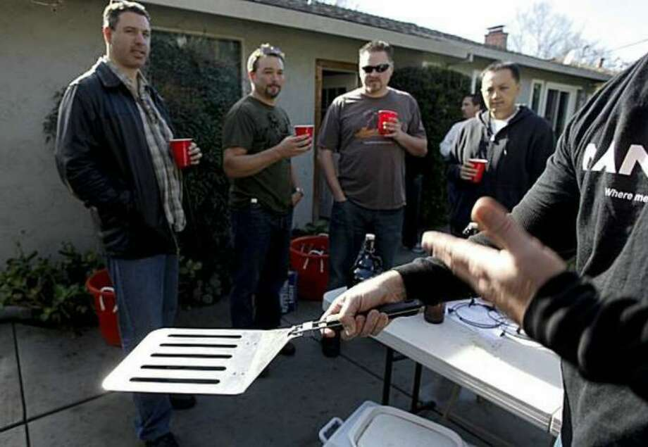 Man Cave salesman John Schaffran displays the $25, four-burger spatula that was one among many Man Cave barbecue products, which were available at this San Jose backyard sales party for men, a male version of the Tupperware party. Photo: / San Francisco Chronicle