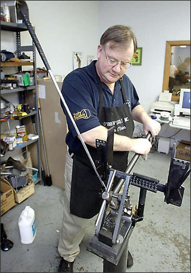 Club maker Tim O'Brien, owner of Club Crafters, adjusts the loft and lie of a club at his academy shop. Photo: Gilbert W. Arias/Seattle Post-Intelligencer