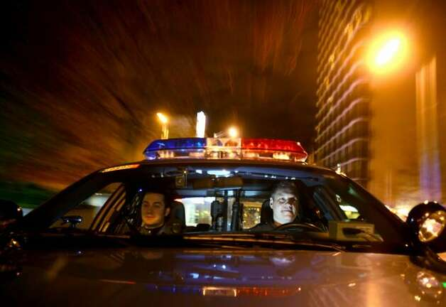 Seattle Police officer Chris Myers (right) drives a patrol car with officer Travis Hill in downtown Seattle on Tuesday. Meyers was named Officer of the Year and has earned the respect of many of his peers. Photo: Joshua Trujillo/seattlepi.com