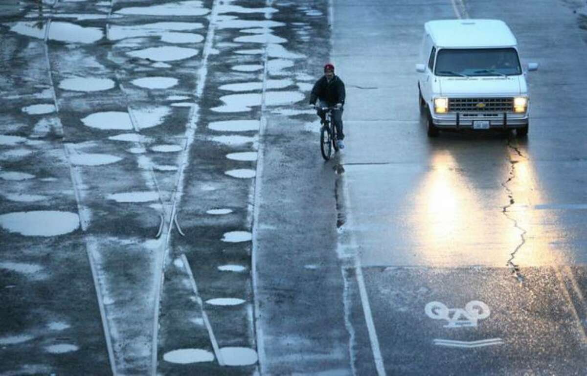 A bicycle rider moves off the road as a van pulls up alongside him on the unfinished section of Seattle's popular Burke-Gilman Trail in the Ballard neighborhood on Thursday. A lawsuit has been filed by cyclists who have been injured on the unfinished section.
