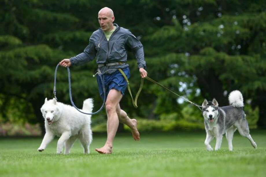 """""""Barefoot"""" Ted McDonald runs with his dogs Hiko, left, and Eddie on June 9 at Volunteer Park in Seattle. Photo: Joshua Trujillo/seattlepi.com"""