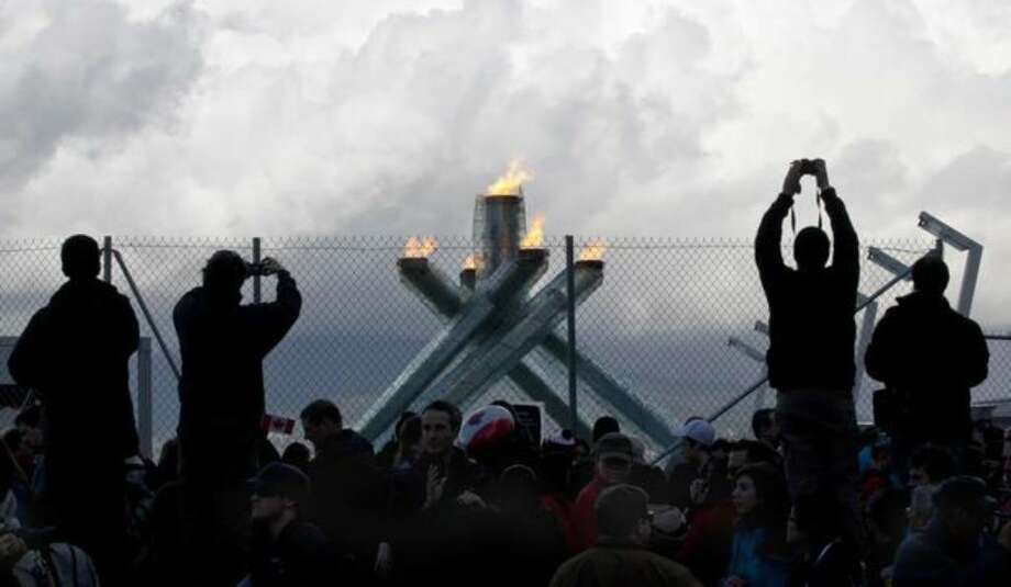 Spectators stand on cement barriers to take souvenir photos of the Olympic cauldron Sunday at the 2010 Vancouver Olympic Winter Games in Vancouver, B.C. (AP Photo/The Canadian Press/Paul Chiasson) Photo: / Associated Press