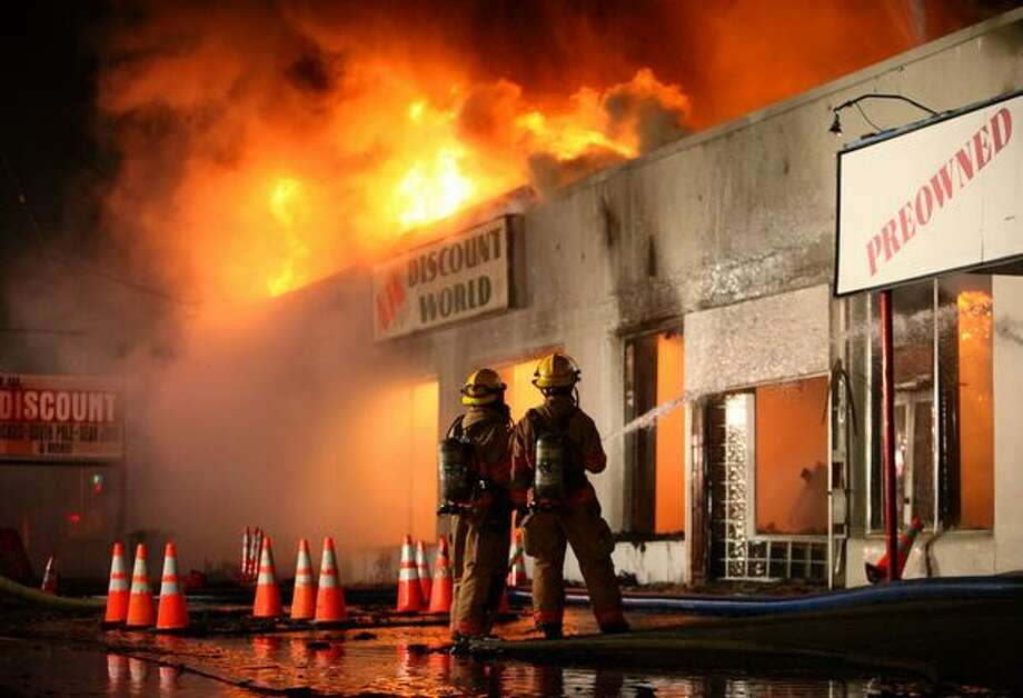 Firefighters battle a three-alarm fire in a vacant building on Aurora Avenue North in Shoreline last week. The fire was later ruled arson. Photo: Joshua Trujillo/seattlepi.com