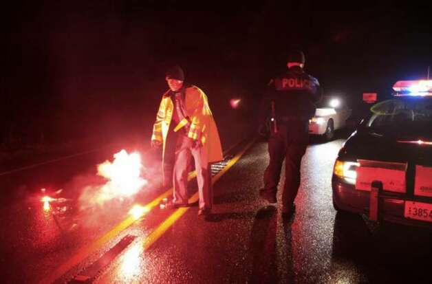 Washington State Patrol and Lakewood police officers light flares at a roadblock near the scene of a shooting that involved two Pierce County Sheriff's deputies, Monday, Dec. 21, 2009, near Eatonville. (AP Photo/Ted S. Warren) Photo: / Associated Press