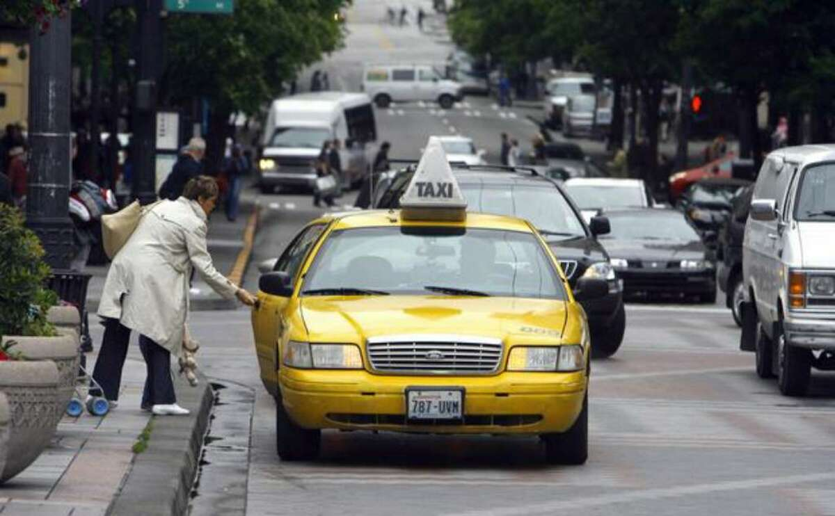 A woman grabs a Yellow Cab in front of Westlake Center in downtown Seattle in this June 2008 file photo.