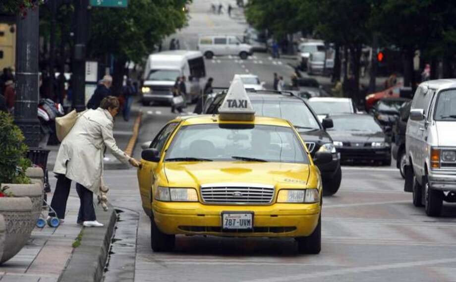 A woman grabs a Yellow Cab in front of Westlake Center in downtown Seattle in this June 2008 file photo. Photo: / P-I File