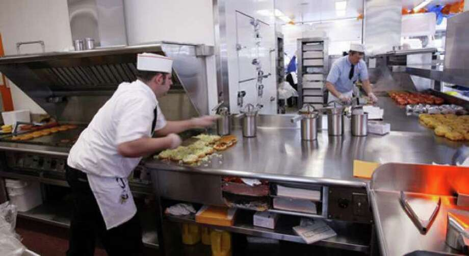 Troy Harper, left, working the expanded Wallingford hamburger grill, and Jerry Frampton, working on the old grill, whip out Dick's deluxe burgers for the lunch-time crowd, April 27, 2007. Photo: Seattlepi.com File