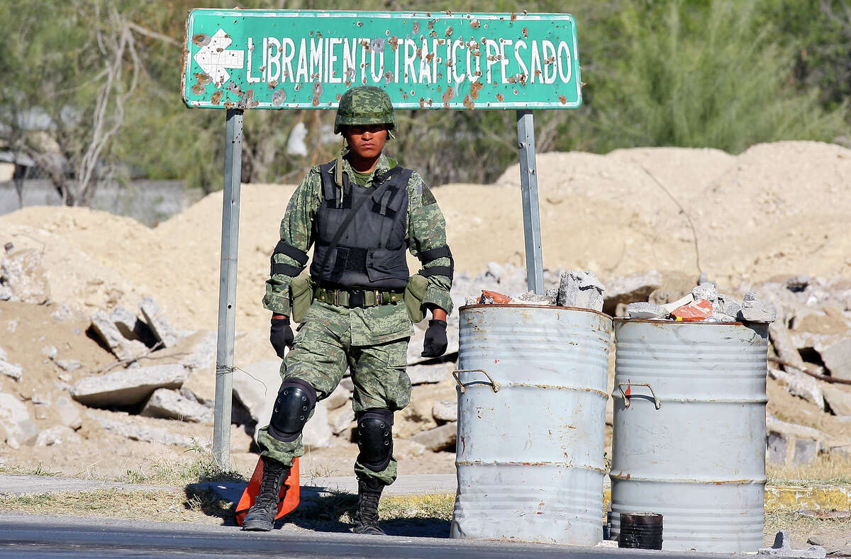 A Mexican army soldier stands near a bullet-riddled sign at a checkpoint to the entrance of Ciudad Mier, Mexico.