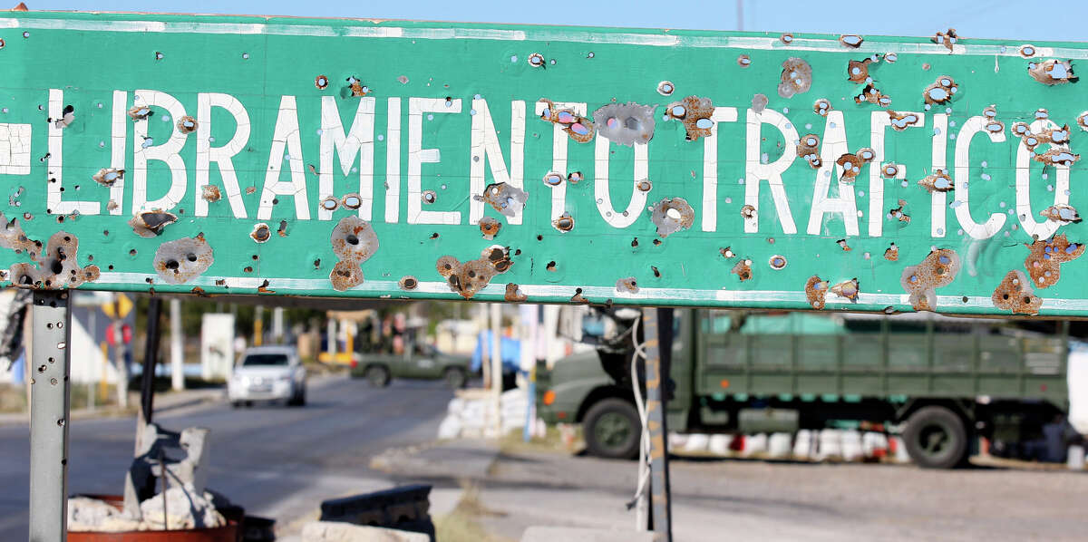 A bullet-riddled sign at a checkpoint to the entrance of Ciudad Mier, Mexico. The city has been under siege for months by warring drug cartels.