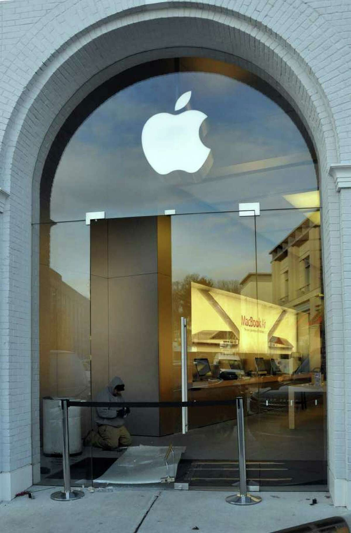 A man repairs the broken glass door at the Apple Store on Greenwich Avenue on Tuesday, Dec. 14, 2010.