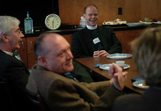 From left; Geoff Hahneman of St. John's Episcopal Church, Kevin Wallin of St. Augustine's Cathedral, Brian Schofield-Bodt of the Council of Churches of Greater Bridgeport, and Sara Verasco of United Congregational Church chat during a planning luncheon for the Week of Prayer for Christian Unity at the Council of Churches offices in Bridgeport. 1/15/09 Photo: Brian A. Pounds / Connecticut Post