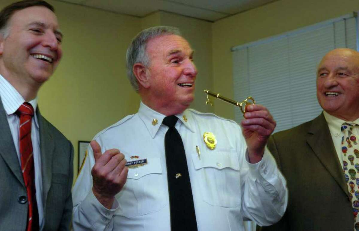 Fire Chief Richard Felner, holding a key to the city, gestures to Ken Flatto, First Selectman of the Town of Fairfield, as Dick Popilowski, right, looks on during a presentation honoring Felner's 50 years of service Wednesday February 4, 2009 at Independence Hall in Fairfield, Conn.