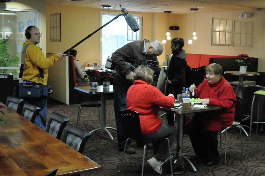 Linda Zoppa, of Southbury, is filmed by ABC News at the Windows Cafe in Walnut Hill Church, in Bethel as part of a primetime segment on weight loss. From left, standing, Mark Suse, Tom Manning and Rashida Johnson, all from ABC. Seated from left Carol Bonanni of Ridgefield and Zoppa. Pictured on Mon. Dec. 13, 2010. Photo: Lisa Weir / The News-Times Freelance
