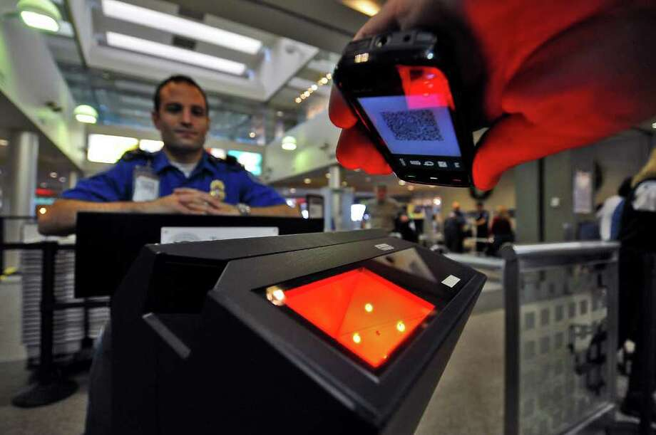 Lead Transportation Security Officer Frank Genovesi, left,  watches as a colleague demonstrates a new scanner at the security screening checkpoint as it scans a barcode on a smartphone, above, simulating an airline passenger boarding pass during a demonstration of how the new scanner will operate when installed and in use at Albany International Airport in Colonie, NY  on Wednesday December 15, 2010. The smartphone will end up being placed a few inches closer to the scanner in order for it to read the barcode.  ( Philip Kamrass / Times Union ) Photo: Philip Kamrass