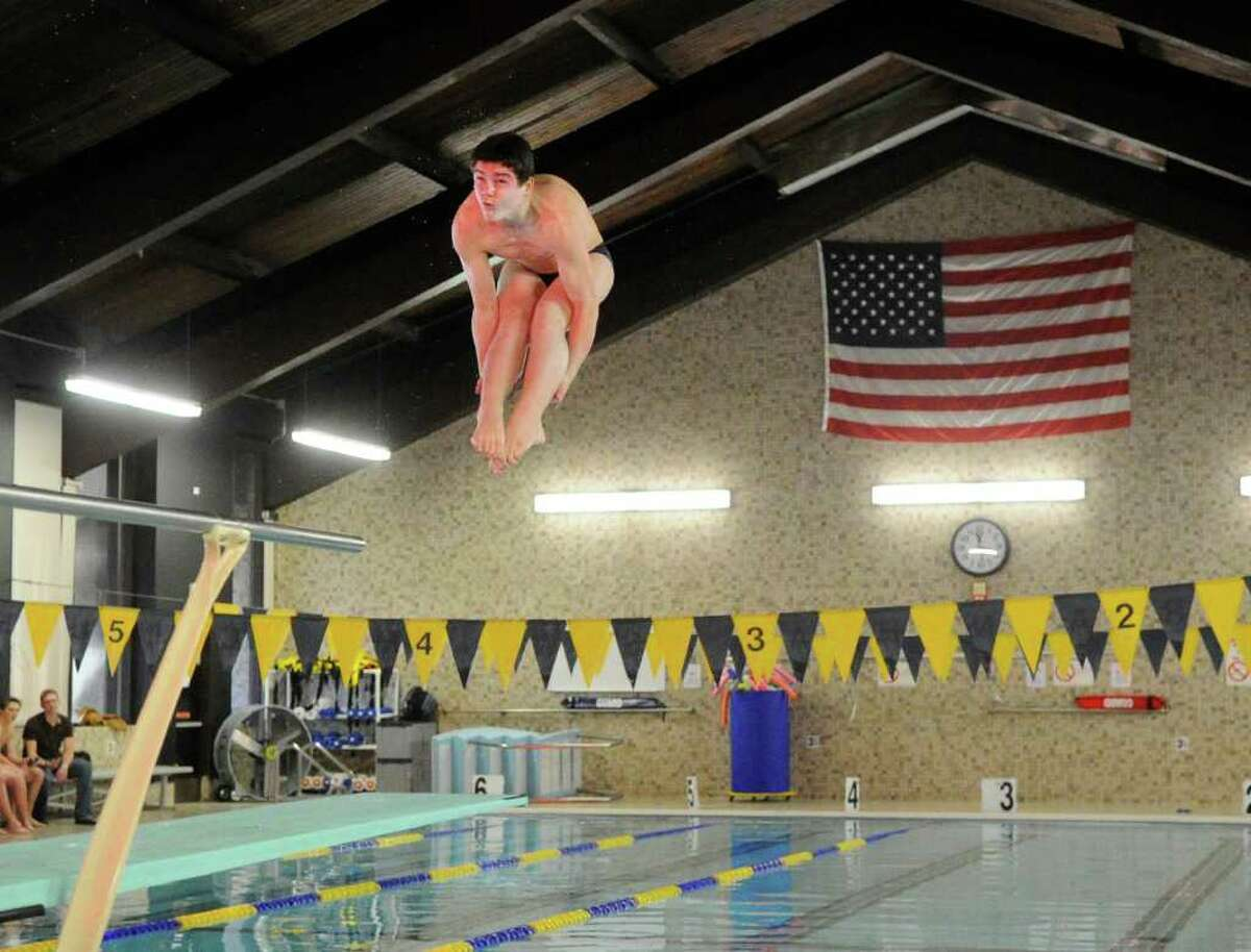 Darien High School diver Jake Bowtell hangs in the air above the pool during meet against Greenwich High School at the Darien YMCA, Wednesday afternoon, Dec. 15, 2010.