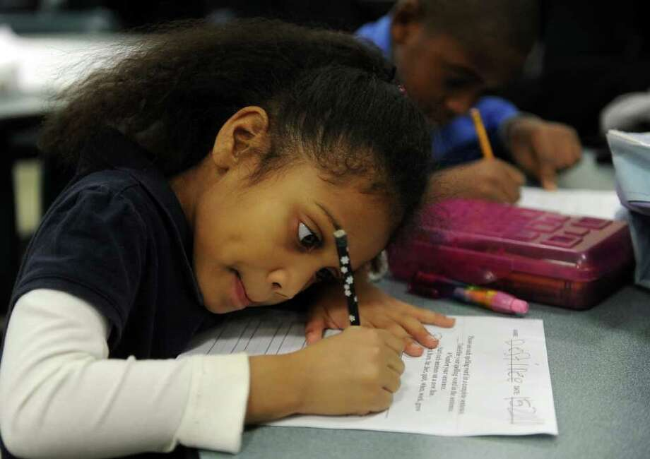 Destinee Mercer, 5, front, and Jerry Johnson, 8, back, work on their homework during Wednesday's Commpact meeting at Bassick High School on December 15, 2010. Photo: Lindsay Niegelberg / Connecticut Post