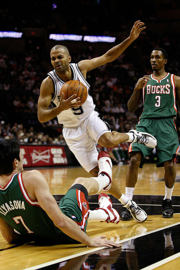 Spurs guard Tony Parker gets tangled up with Bucks forward Ersan Ilyasova during the first half at the AT&T Center, Wednesday, Dec. 15, 2010. In back is Bucks guard Brandon Jennings. Photo: JERRY LARA/glara@express-news.net, Express-News