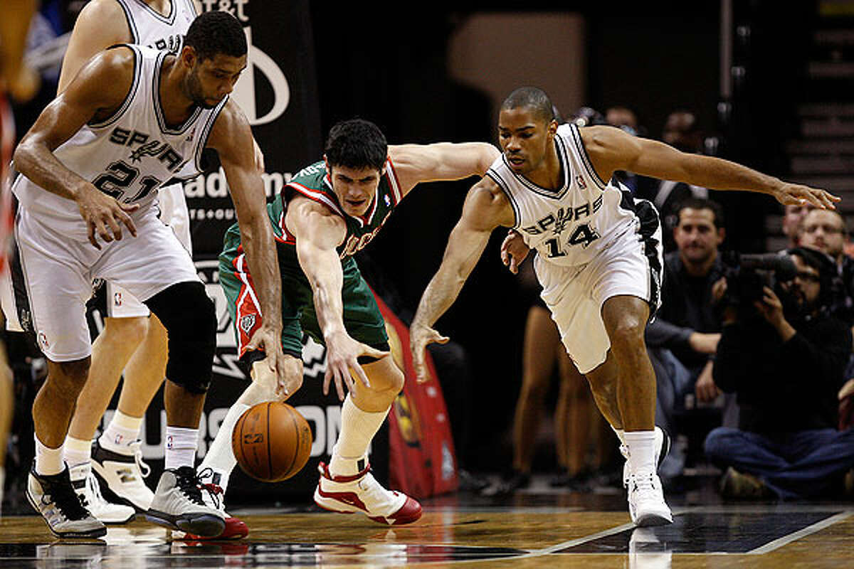 The Spurs' Tim Duncan (left) and Gary Neal keeps the ball away from the Bucks' Ersan Ilyasova during the first half at the AT&T Center, Wednesday, Dec. 15, 2010.