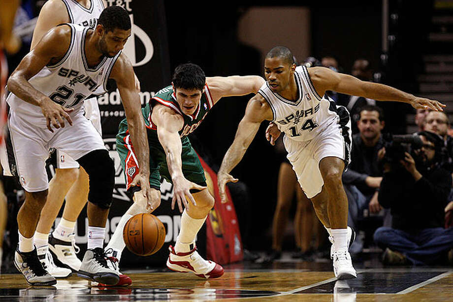 The Spurs' Tim Duncan (left) and Gary Neal keeps the ball away from the Bucks' Ersan Ilyasova during the first half at the AT&T Center, Wednesday, Dec. 15, 2010. Photo: JERRY LARA/glara@express-news.net