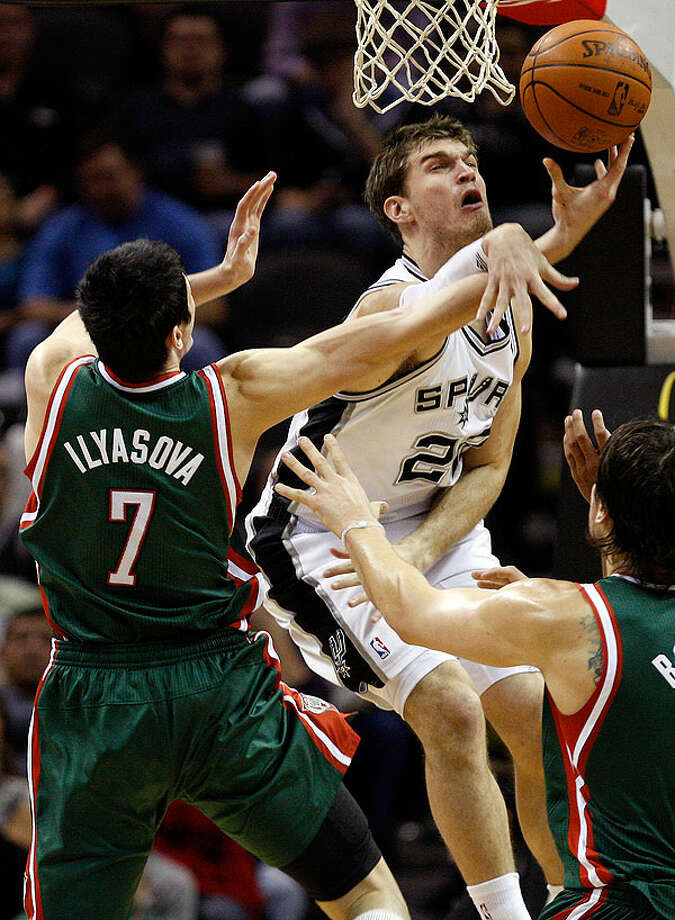 The Spurs' Tiago Splitter tries to block a shot from the Bucks' Ersan Ilyasova during the first half at the AT&T Center, Wednesday, Dec. 15, 2010. Photo: JERRY LARA/glara@express-news.net