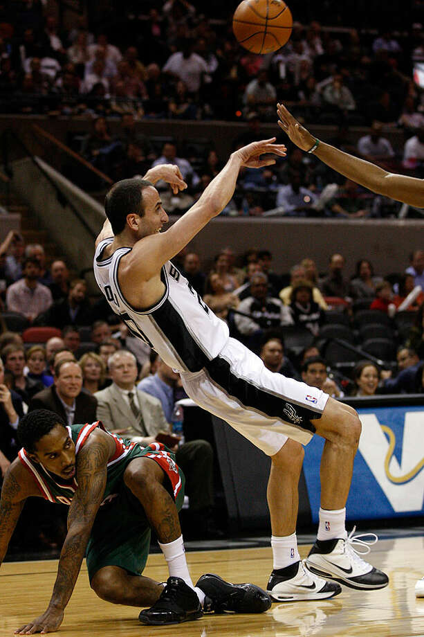 The Spurs' Manu Ginobili passes the ball to the outside perimeter after a rebound with the Bucks' Brandon Jennings on the floor during the first half at the AT&T Center, Wednesday, Dec. 15, 2010. Photo: JERRY LARA/glara@express-news.net, Express-News