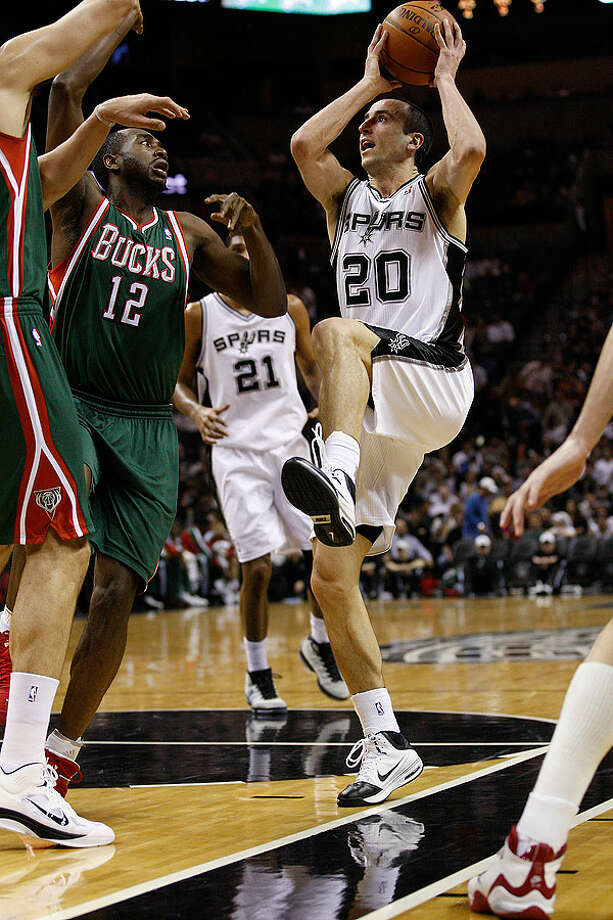 The Spurs' Manu Ginobili drives the ball as the Bucks' Luc Mbah a Moute defends during the first half at the AT&T Center, Wednesday, Dec. 15, 2010. Photo: JERRY LARA/glara@express-news.net, Express-News