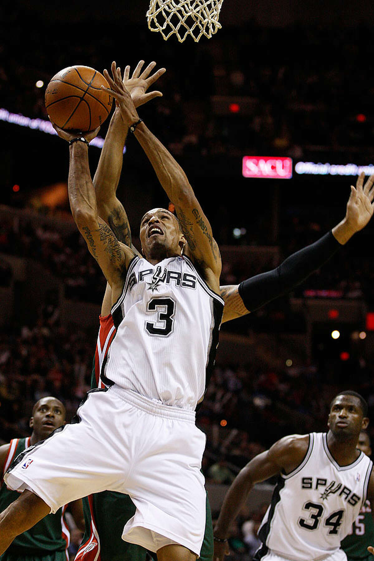 The Spurs' George Hill goes for two under pressure from the Bucks' Drew Gooden during the first half at the AT&T Center, Wednesday, Dec. 15, 2010.