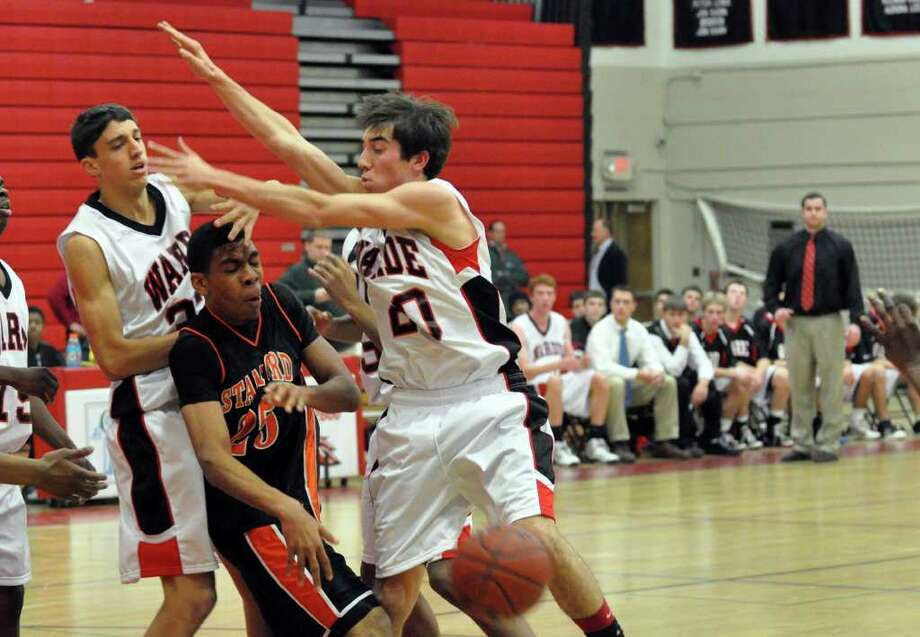 Stamford's Terrance Ditimi, center, passes the ball as Warde's Sal Siciliano and Matt McTague, far right, defend during the boys basketball game at Warde on Wednesday, Dec. 15, 2010. Photo: Amy Mortensen / Connecticut Post Freelance