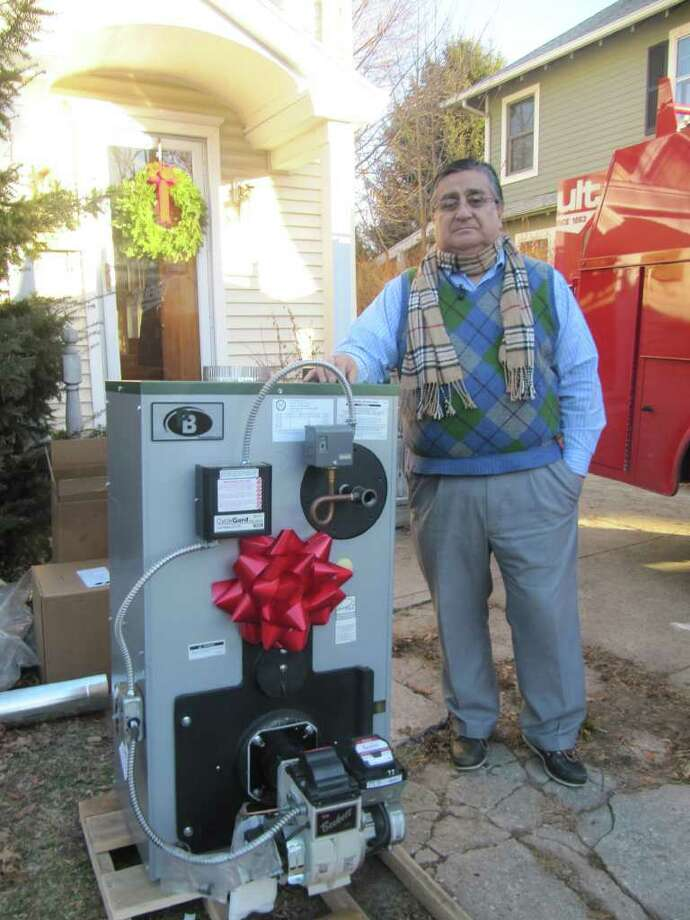 Fairfield resident Pepe Soto-Ortiz stands besides the new boiler he and his wife Anita received from Gault Energy on Thursday morning. The couple won Gault's 2010 Oldest Boiler Contest. Photo: Kirk Lang / Fairfield Citizen