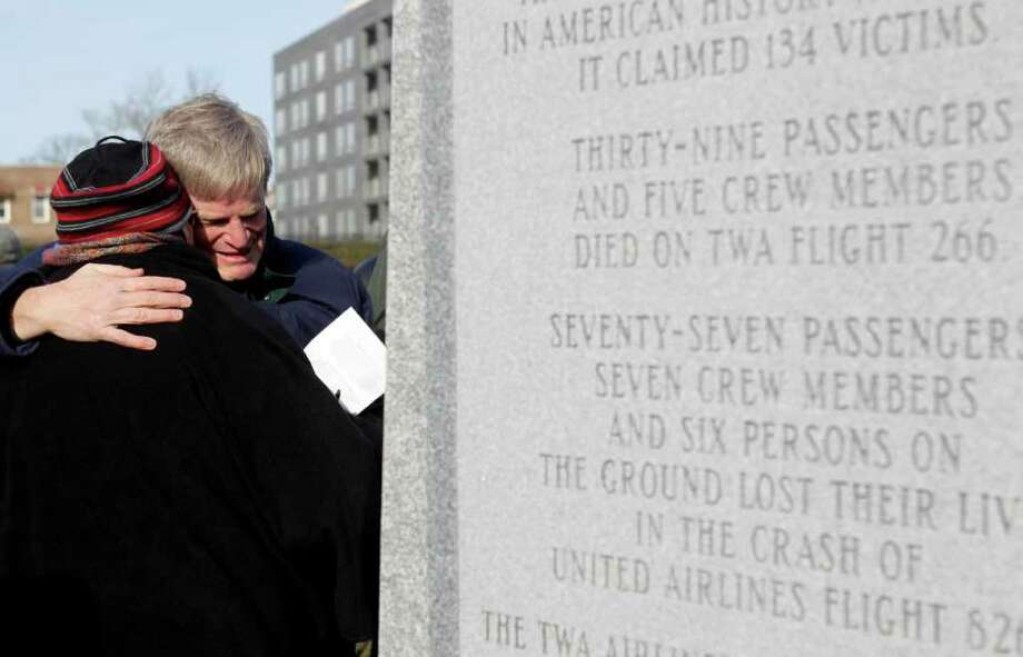 Kevin Root, right, a Greenwich resident, hugs Fern Liddy near a just-unveiled monument to the victims of the midair plane collision on Dec. 16, 1960, in Green-Wood Cemetery in New York, Thursday, Dec. 16, 2010. Both of Root's parents, Sam and Florence Root, were killed in the collision; Sam Root was also Liddy's employer at the time. (AP Photo/Seth Wenig) Photo: Seth Wenig, AP / AP