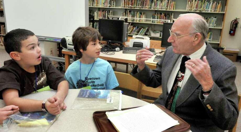 """Kyle Burbank, left, and Kyle Cascone, fourth-graders at Hawley Elementry School in Newtown, talk with Philip Michael, 93, during a program called """"Book Buddies"""" Thursday, Dec. 16, 2010. Photo: Michael Duffy / The News-Times"""
