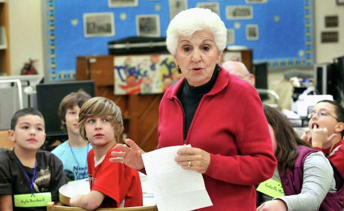 """Kyle Burbank, left, and, Brennan Mayer, left center, are among fourth-graders at Hawley Elementry School in Newtown listening to Connie Scigimpaglia, 82, during a program called """"Book Buddies"""" Thursday, Dec. 16, 2010."""