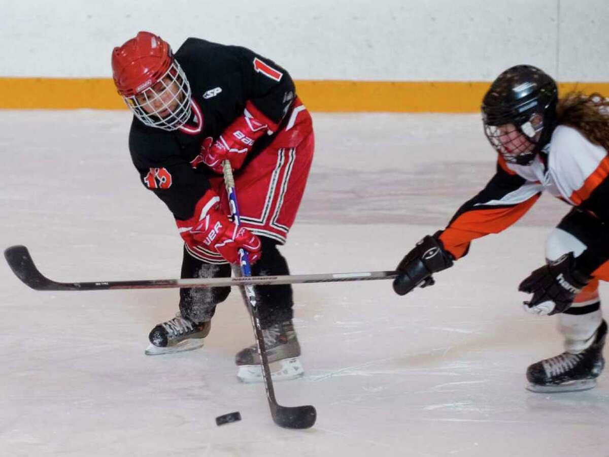 New Canaan's Carla J. Paredes trying to control the puck during a girls hockey game at Ridgefield. Wednesday, Dec. 15, 2010