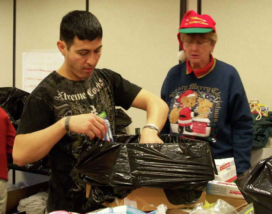 John Julian, left, a member of the Army National Guard who recently returned from a tour of duty in Afghanistan, helps Miriam Zalenski fill a care package that will be shipped to soldiers overseas. Julian himself received several packages from the Fairfield-based group, Project From the Heart. Photo: Genevieve Reilly / Fairfield Citizen