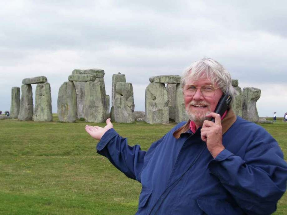 "Fairfield resident Rob Carlson stands in front of England's prehistoric, mysterious circle of upright stones better known as Stonehenge. Carlson, who will debut his ""Rob's Discount Variety"" at the Fairfield Theatre Company this weekend, joked that he wouldn't be surprised if Stonehenge is one day replaced by condominiums. Photo: Contributed Photo / Fairfield Citizen contributed"