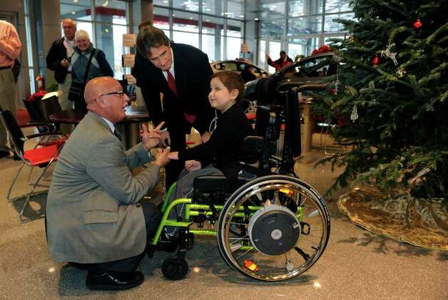 Justin Purviance, 7, of Milford, received an electric wheelchair which was purchased by Robert Crabtree Jr., in center, who owns Colonial Toyota in Milford, Conn.. Crabtree and Tony Candido, Chairman of Concerned Citizens for People With Disabilities, at left, presented Justin with the wheelchair on Thursday December 16, 2010 at Colonial Toyota in Milford, Conn.. Photo: Christian Abraham / Connecticut Post