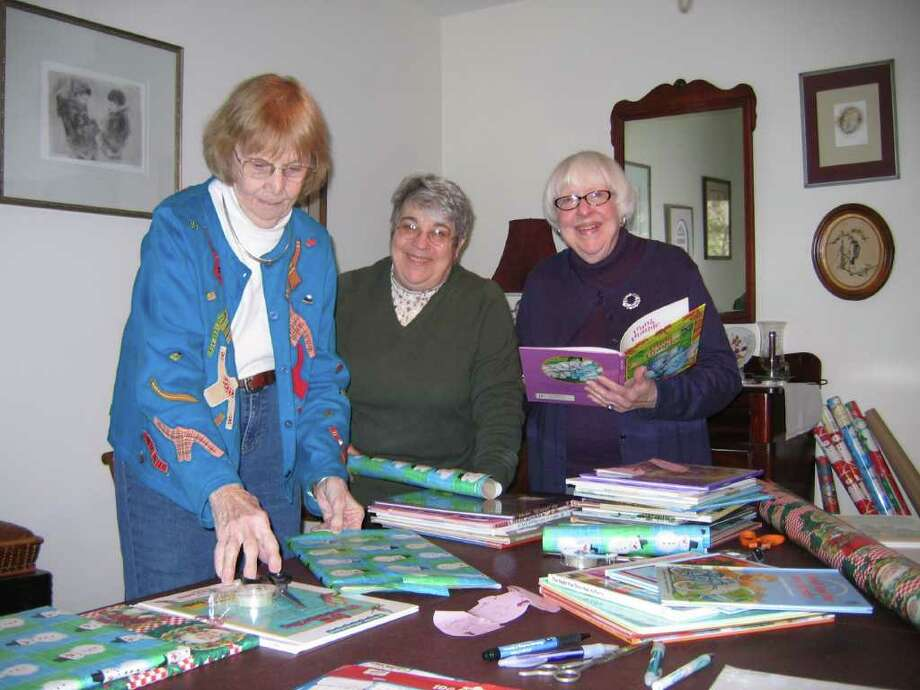 Gift-wrapping books for the Marie Morrison Holiday Childrens Book Project are, from left, Helen Gaige, Niki Mook and Marion Renning. (Photo by Charles C. Morrison)