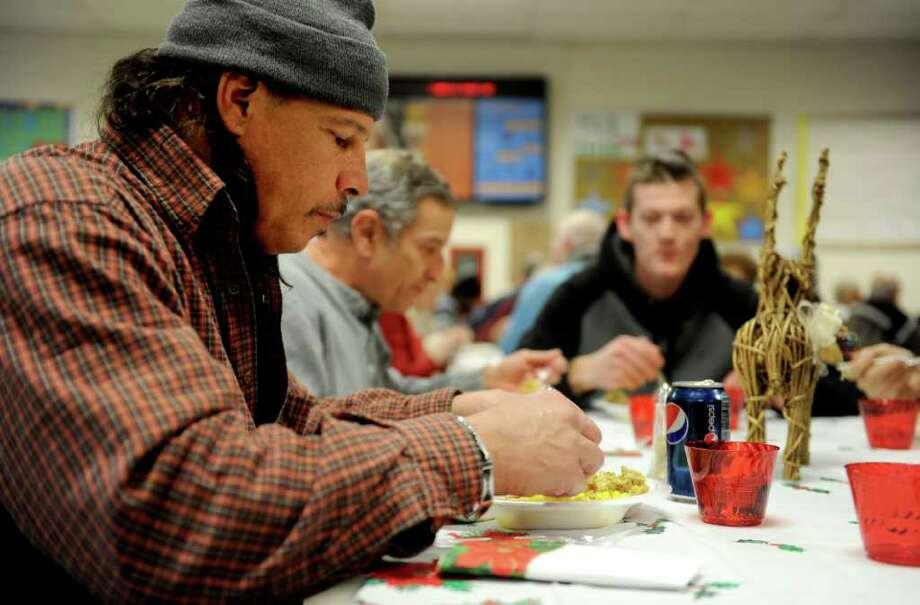 From left, John Verrilli, Gary Onofrio and Mike Barton enjoy a meal during the Holiday Homeless and Elderly Dinner with food prepared by Emmett O'Brien's culinary students on Thursday, December 16, 2010. Photo: Lindsay Niegelberg / Connecticut Post