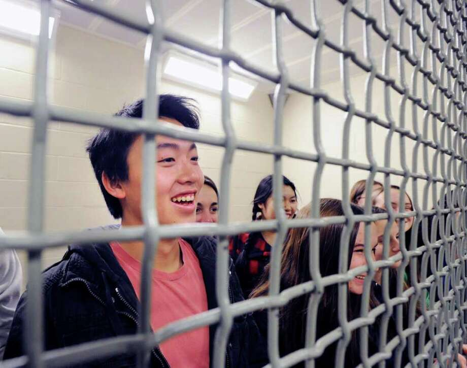 At left, Colin Ng, 16, a Greenwich High School junior and member of the school's Outreach Club, smiles after being placed in lock-up with other club members during a tour of the Greenwich Police Department, Thursday afternoon, Dec. 16, 2010. Photo: Bob Luckey / Greenwich Time