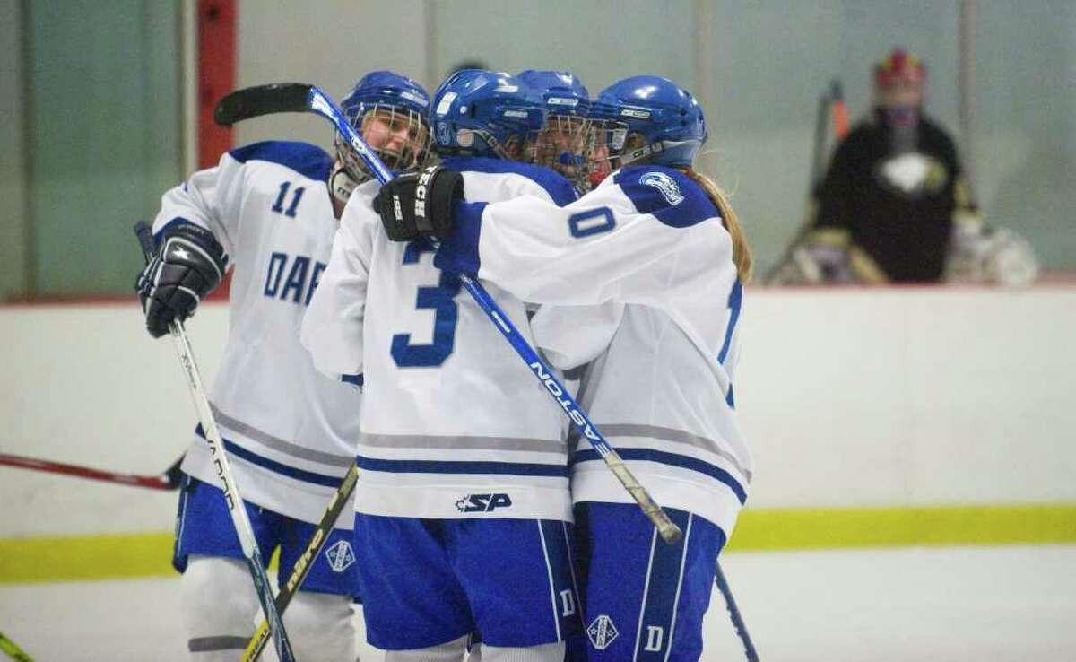 The Darien team congratulates Emma Tuzinkiewicz after her score as Darien High School hosts Trumbull in a girls hockey game at the Darien Ice Rink in Darien, Conn., Thursday, December 16, 2010.
