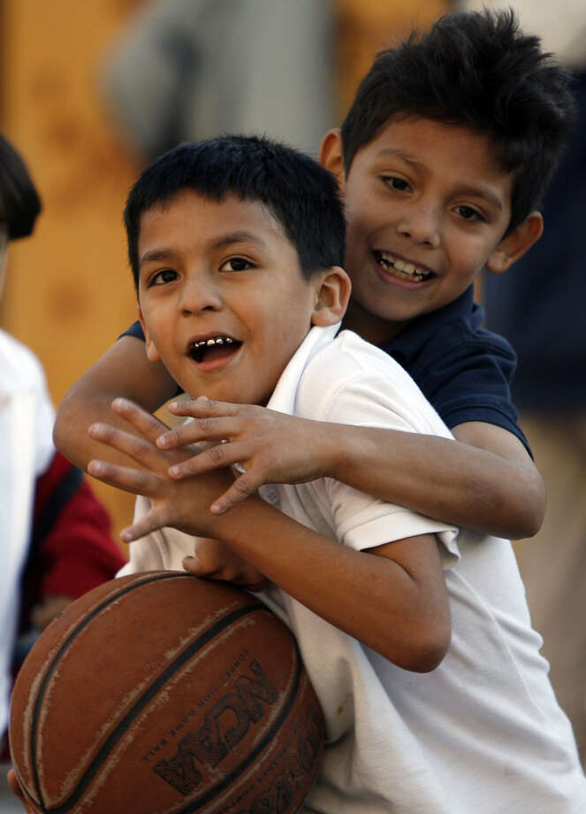 Jose Teran drives to the hoop as Erick Rodriguez defends during an after-school program at the Dan Cook Youth Center, part of the SA Youth nonprofit organization. Photo: MICHAEL MILLER/mmiller@express-news.net
