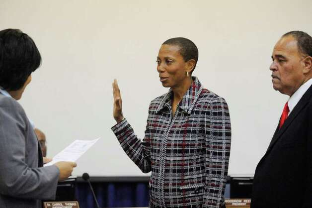 Gwen Ambres, center, is sworn in as the new BISD board member by BISD attorney Melody Chappell, left, with BISD president Woodrow Reece standing at her side. Thursday, December 16, 2010 Valentino Mauricio/The Enterprise Photo: Valentino Mauricio / Beaumont