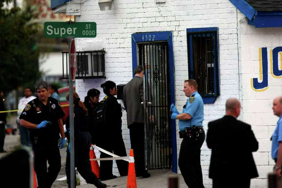 Houston police officers and detectives investigate the shooting of three suspected robbers by Ramon Castillo at his jewelry store on the corner of Canal and Super Street, east of downtown. Photo: Johnny Hanson, Staff / Houston Chronicle
