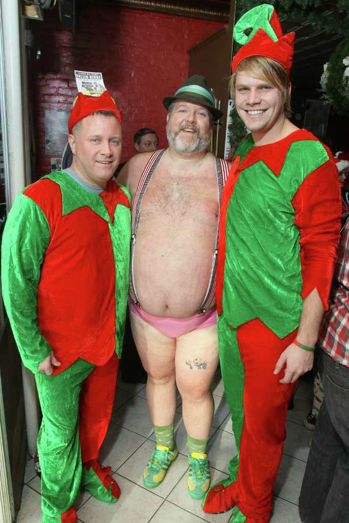 Jim Larson, race director for the Santa Speedo Sprint, with his elves, Scott Rhubright, left, and Bradford Stevens. (Joe Putrock / Special to the Times Union)