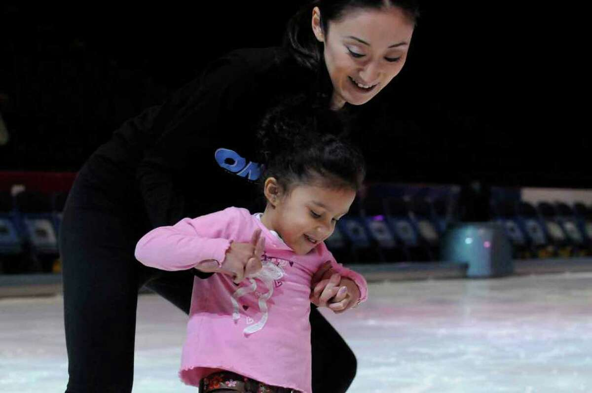 Disney on Ice Toy Story 3 skater Yukari Koyanagi helps 4-year-old Kali Wall of Menands around the ice during a Disney on Ice Make-A-Wish skating Party at the Times Union Center in Albany. (Michael P. Farrell/Times Union)