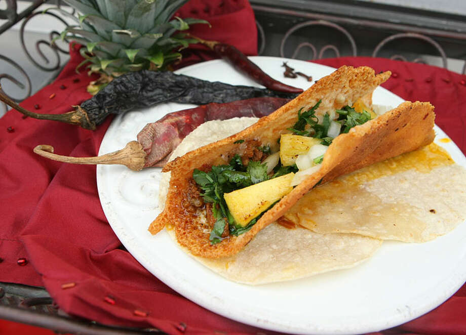La Costra del Güero includes some white melting cheese on three corn tortillas topped with carne al pastor.
